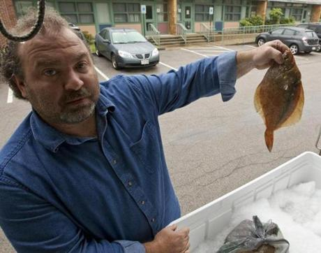 "Nick Vitale, a deliveryman for Cape Ann Fresh Catch, with a yellowtail flounder in the Morse School parking lot in Cambridge, where ""CSF"" customers pick up their seafood."